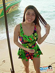 Standing On Beach Wearing Sundress Playing With Her Hair