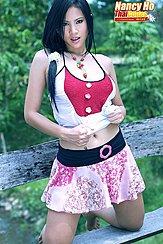 Long Hair In Ponytail Over Her Shoulder Pulling Her Top Up Wearing Skirt Kneeling On Bench