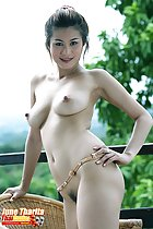 Kneeling on wicker chair naked hand on hip firm breasts with pert erect nipples