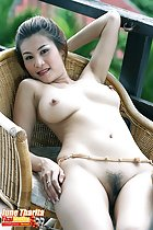 June Tharita lying on wicker chair arm raised bare breasts thighs pressed together concealing her pussy