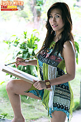 Balancing Canvas On Her Knee Holding Paint Brush